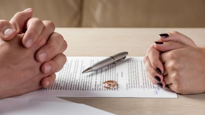 Man and woman sitting at table with hands folded and divorce paper, pen, rings, and divorce decree on table.